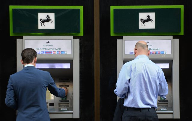 Members of the public use cash machines at a branch of Lloyds Bank in the City of London