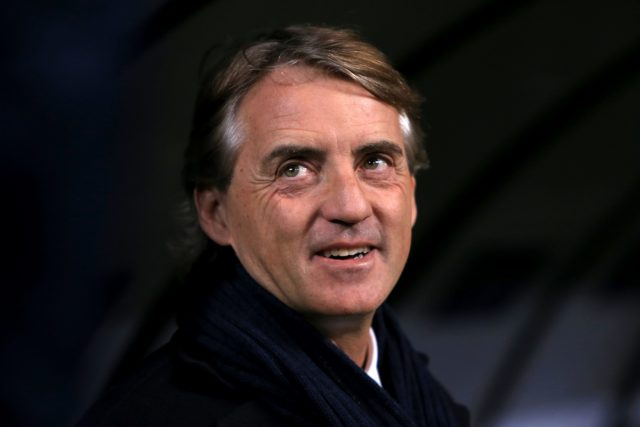 Roberto Mancini smiles as he looks up to the stands