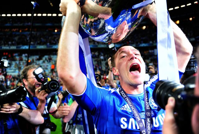 John Terry celebrates with the Champions League trophy in full kit despite being banned for the final