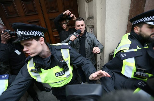 Tommy Robinson seeks protection from the police near Trafalgar Square in London, during a counterprotest by UAF