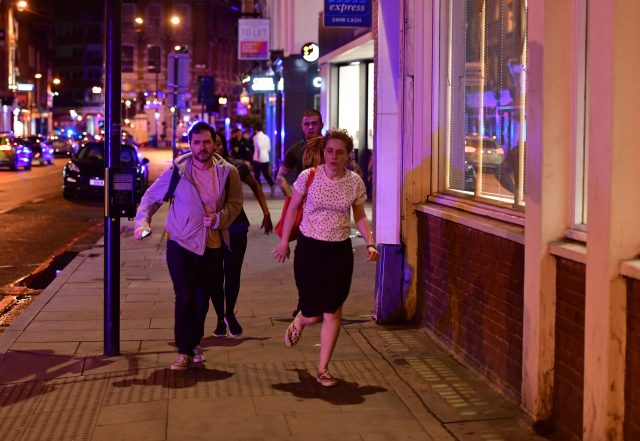 People run down Borough High Street to flee (Dominic Lipinski/PA)