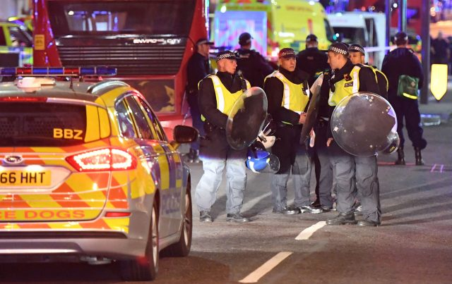 Police officers with riot shields are on Borough High Street