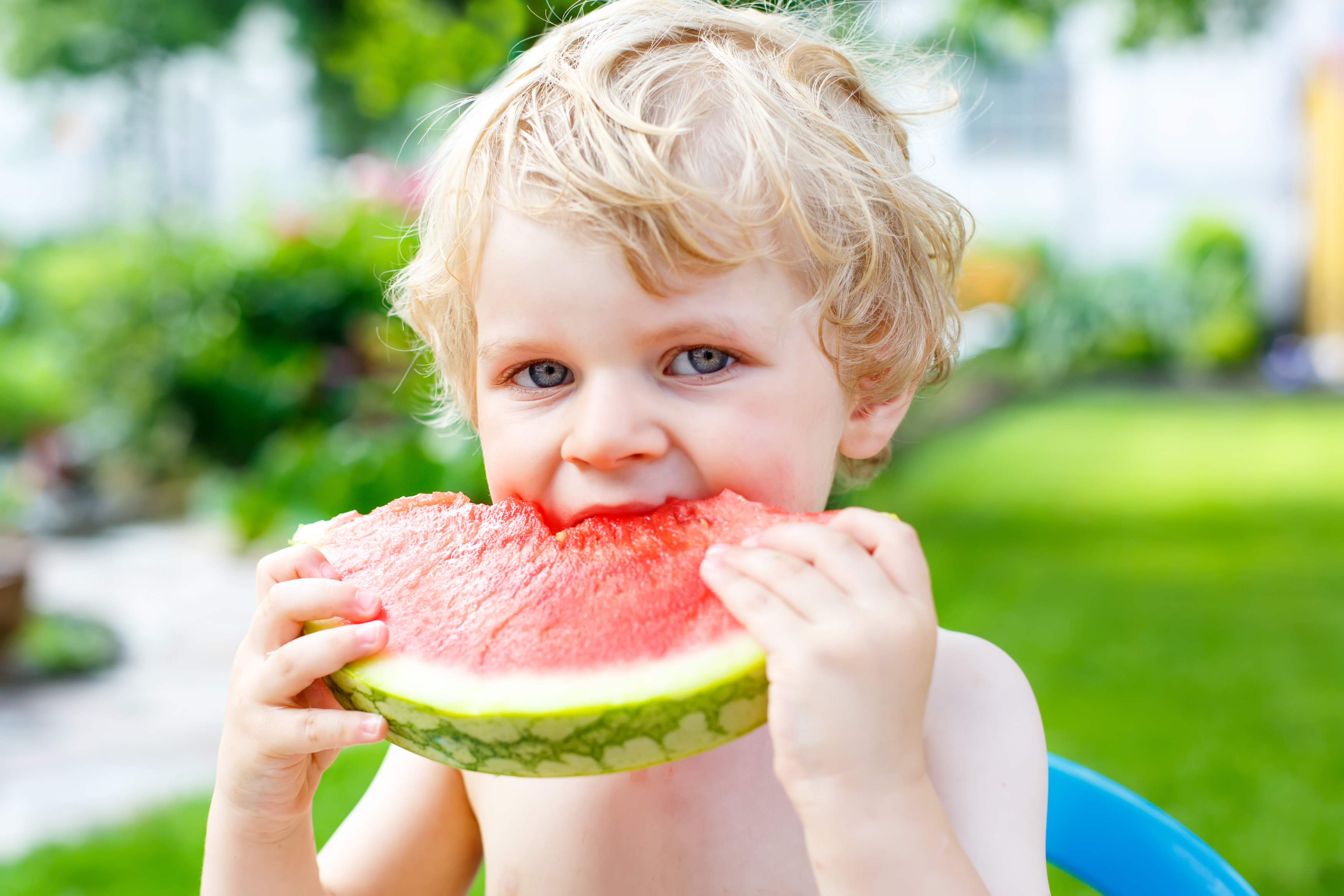 A boy eating a slice of watermelon
