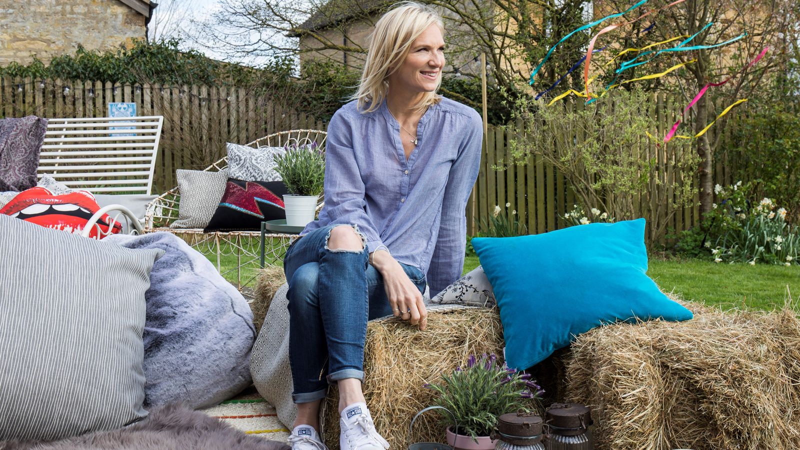 Jo Whiley in her garden with hay bales, cushions and benches (PA/Hillarys Blinds)