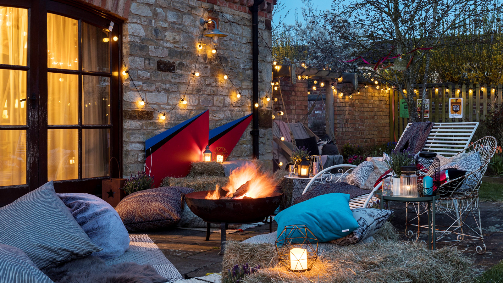 Jo Whiley's garden, decorated in festival style with a home made Ziggy Stardust lightning sign, fairy lights, a fire pit, and casual seating (PA/Hillarys Blinds)