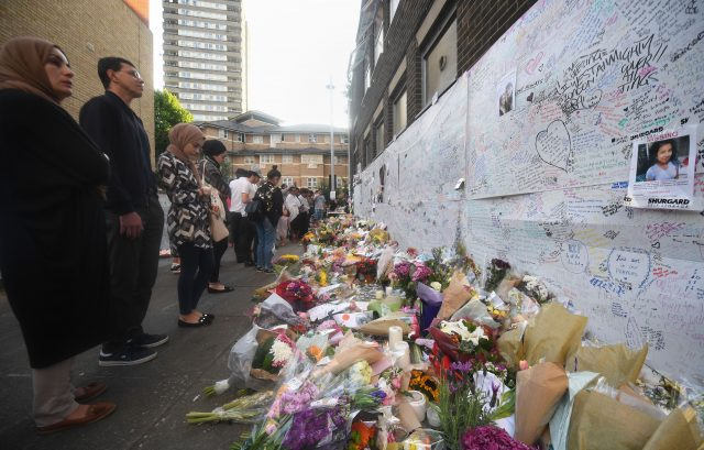 People look at tributes near Grenfell Tower in west London