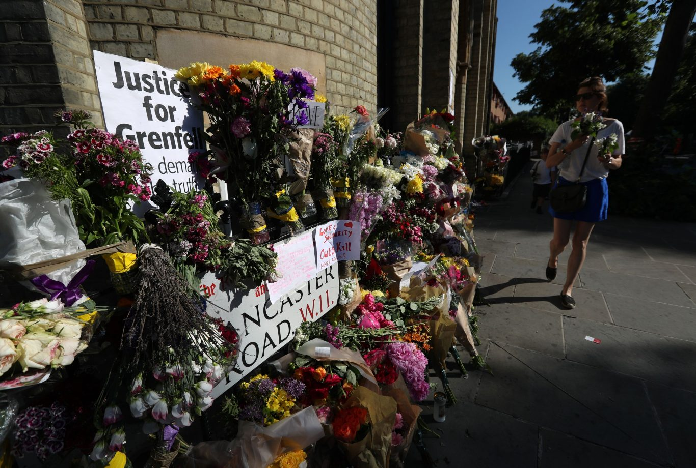 People walk past floral tributes outside Notting Hill Methodist Church (Jonathan Brady/PA)