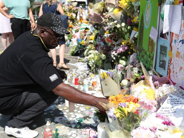 A man lays flowers outside Notting Hill Methodist Church (Jonathan Brady/PA)