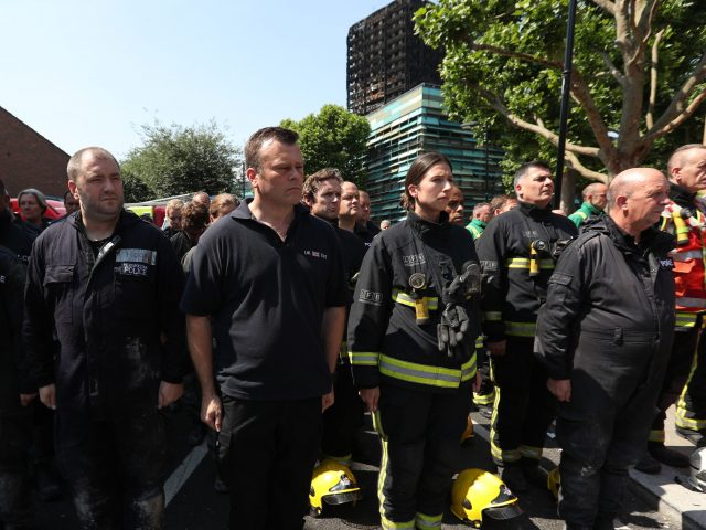 Members of the emergency services observe a minute's silence (Jonathan Brady/PA)