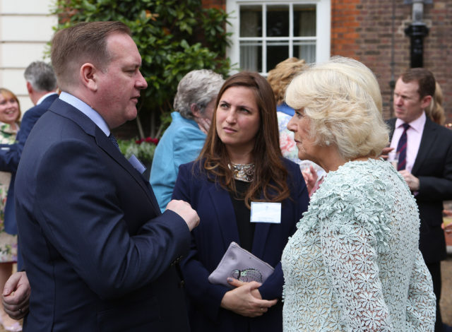 The Duchess of Cornwall speaks to EastEnders producer(formally the Archers) Sean O'Connor (left) and Louiza Patikas who plays Helen in the Archers (centre), during a reception for survivors of domestic abuse
