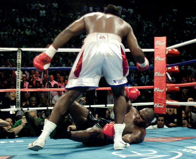 Lennox Lewis stands over Mike Tyson in their 2002 fight