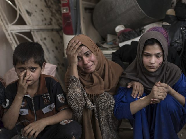 Iraqi civilians wait to be led out of Mosul (Felipe Dana/AP)