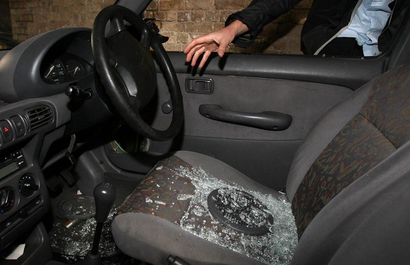 A hand reaches into a car through a broken window (Lewis Whyld/PA)