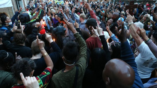 People attend a vigil to mark four weeks since the Grenfell Tower fire
