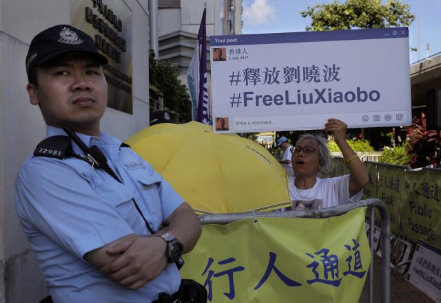 Police watch demonstrators outside the Chinese liaison office in Hong Kong (Vincent Yu/AP)
