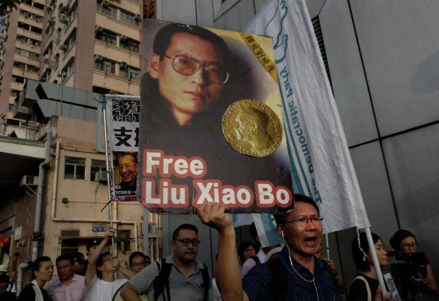 Protesters display portrait of jailed Chinese Nobel Peace laureate Liu Xiaobo (AP)