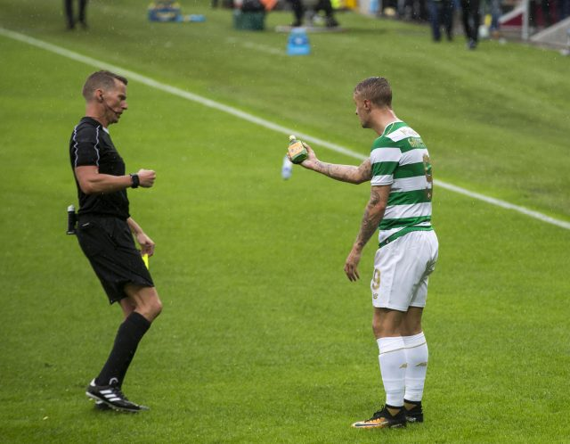 Leigh Griffiths shows the referee an empty bottle of Buckfast after it was thrown at him