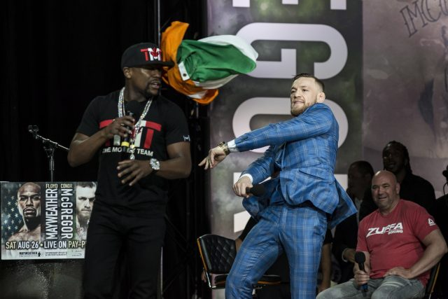 Conor McGregor, right, throws an Irish flag at Floyd Mayweather