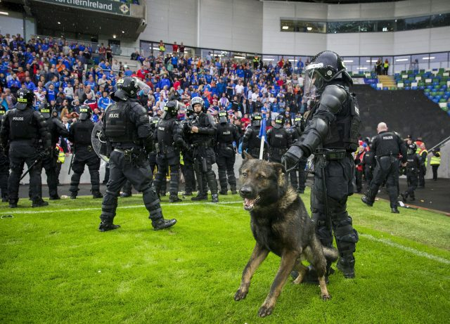 PSNI K-9 unit and police in riot gear stand on the pitch in front of Linfield supporters following the UEFA Champions League Qualifying, Second Round, First Leg match at Windsor Park, Belfast.