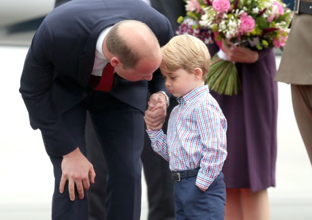 Prince George holding the hand of his father, the Duke of Cambridge