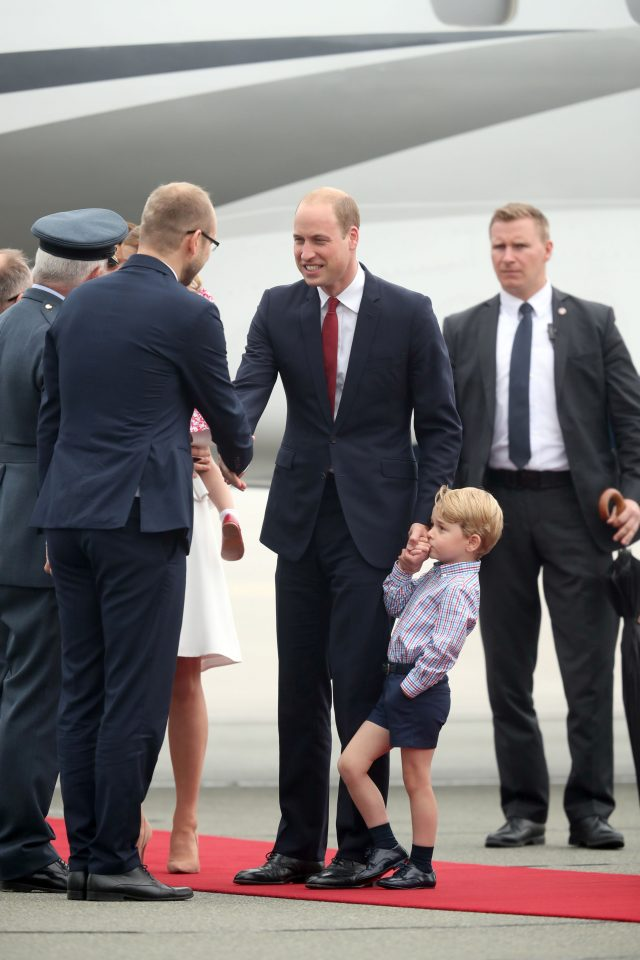 Prince George holds the hand of his father