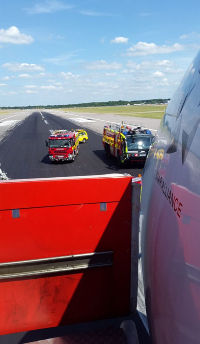 Emergency vehicles next to an Air Canada Rouge plane with a burst tyre