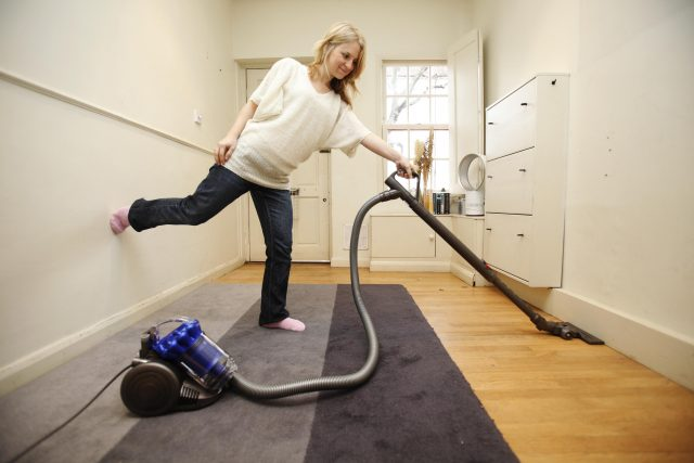 A woman uses a vacuum cleaner