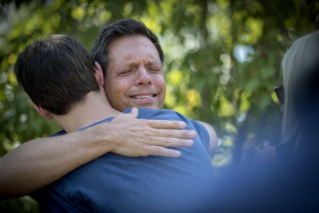 Don Damond is comforted by friends and family