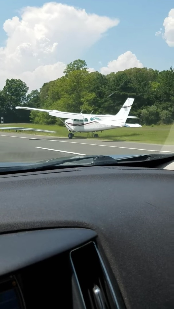 Driver catches plane landing on a New York freeway.