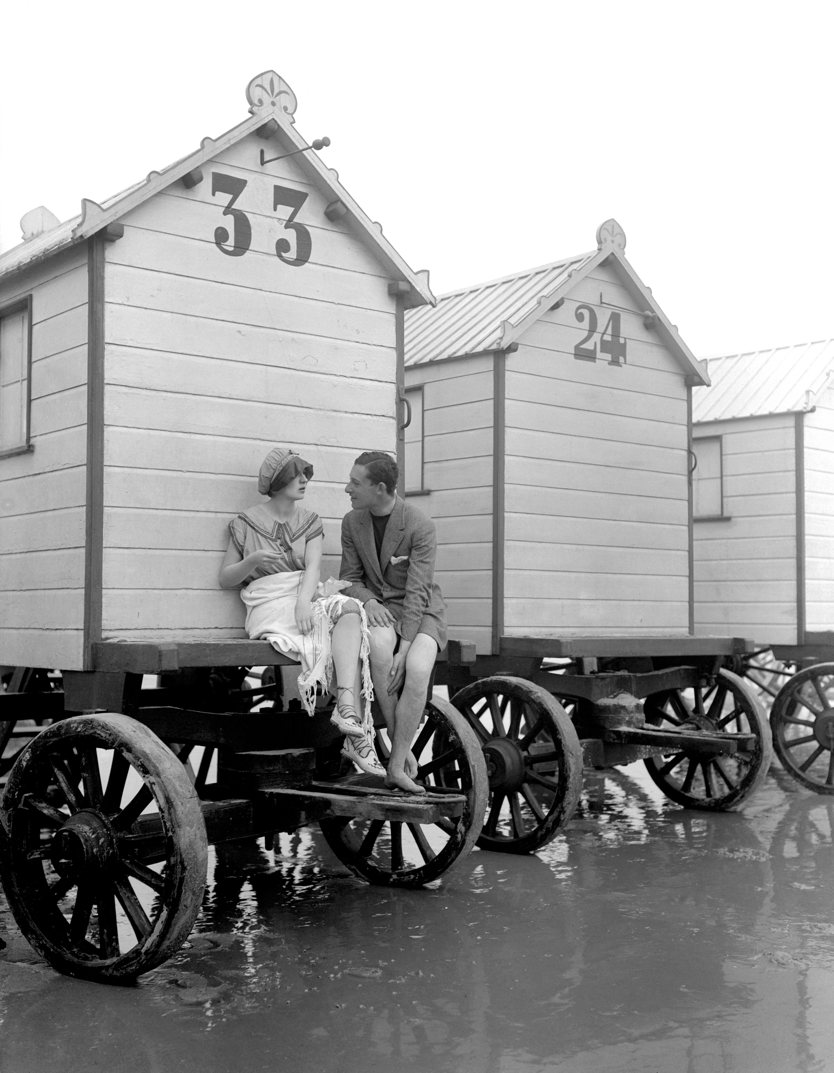 Holidaymakers sit by their beach hut in Margate