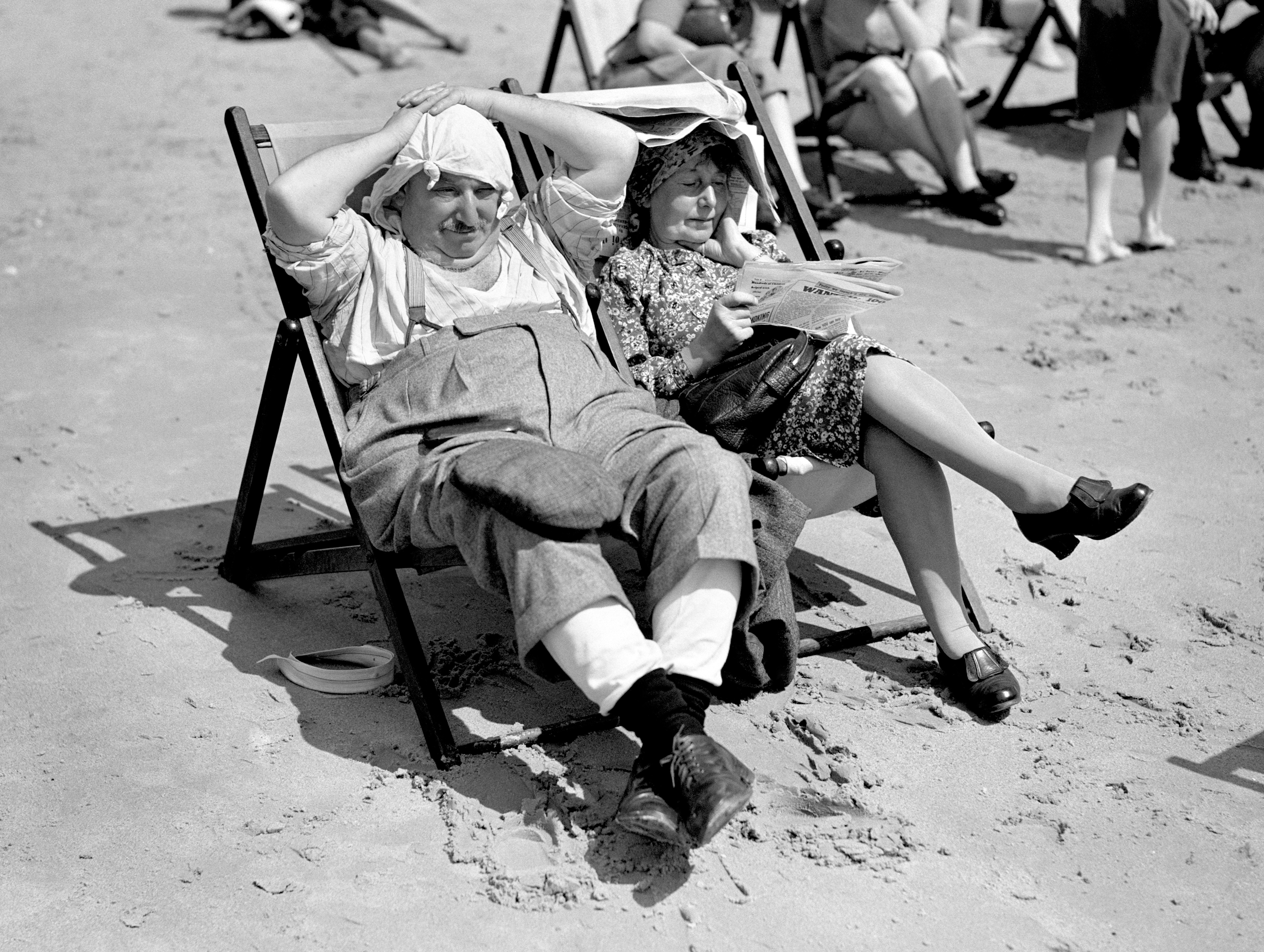 Older holidaymakers sunbathing on Bournemouth beach