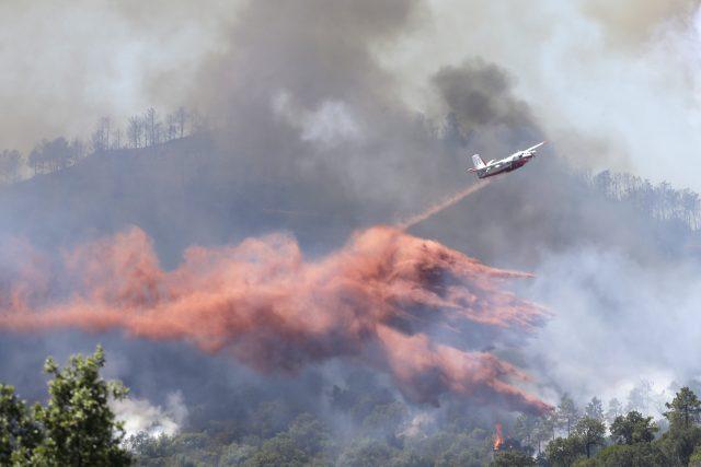 A plane drops fire retardant