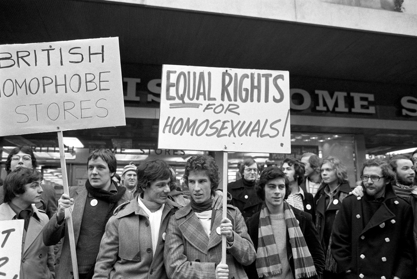 A banner carrying homosexual Tony Whitehead (centre) and his friend John Roman Baker (white scarf) during a protest by supporters of the Campaign for Homosexual Equality at a British Home Stores in London's Oxford Street, over the forced resignation of Mr Whitehead after being shown on TV kissing and cuddling Mr Baker.
