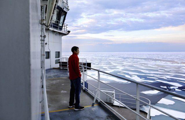 The sky is lit by the sun at midnight as trainee David Kullualik looks over the sea ice of Peel Sound (David Goldman/AP)