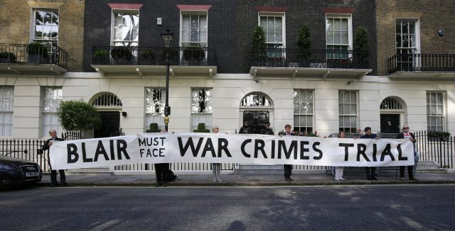 Protesters hold a banner outside the London home of Mr Blair (PA)