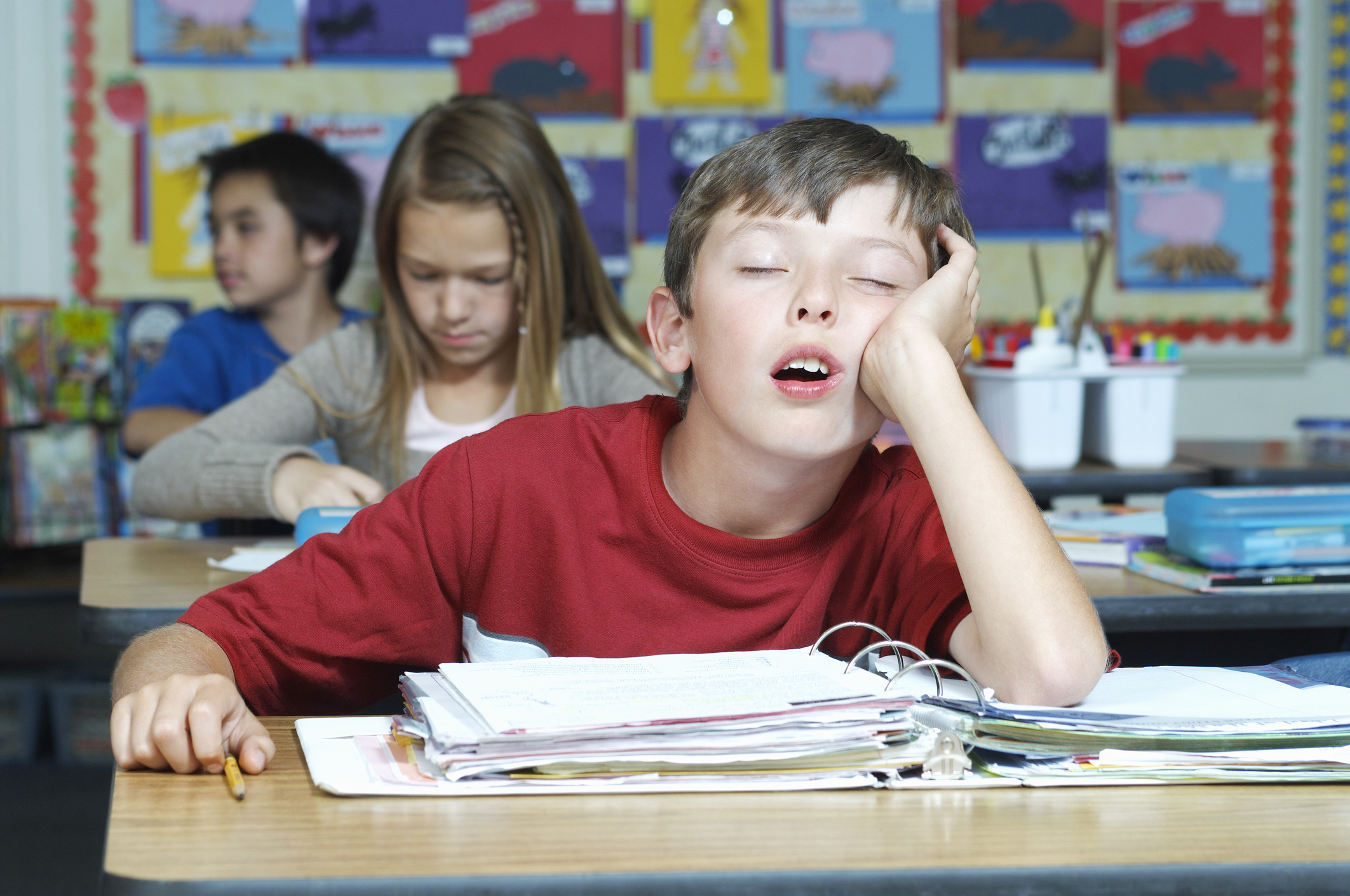 A young boy propped up on his elbow falls asleep at his school desk (Thinkstock/PA)