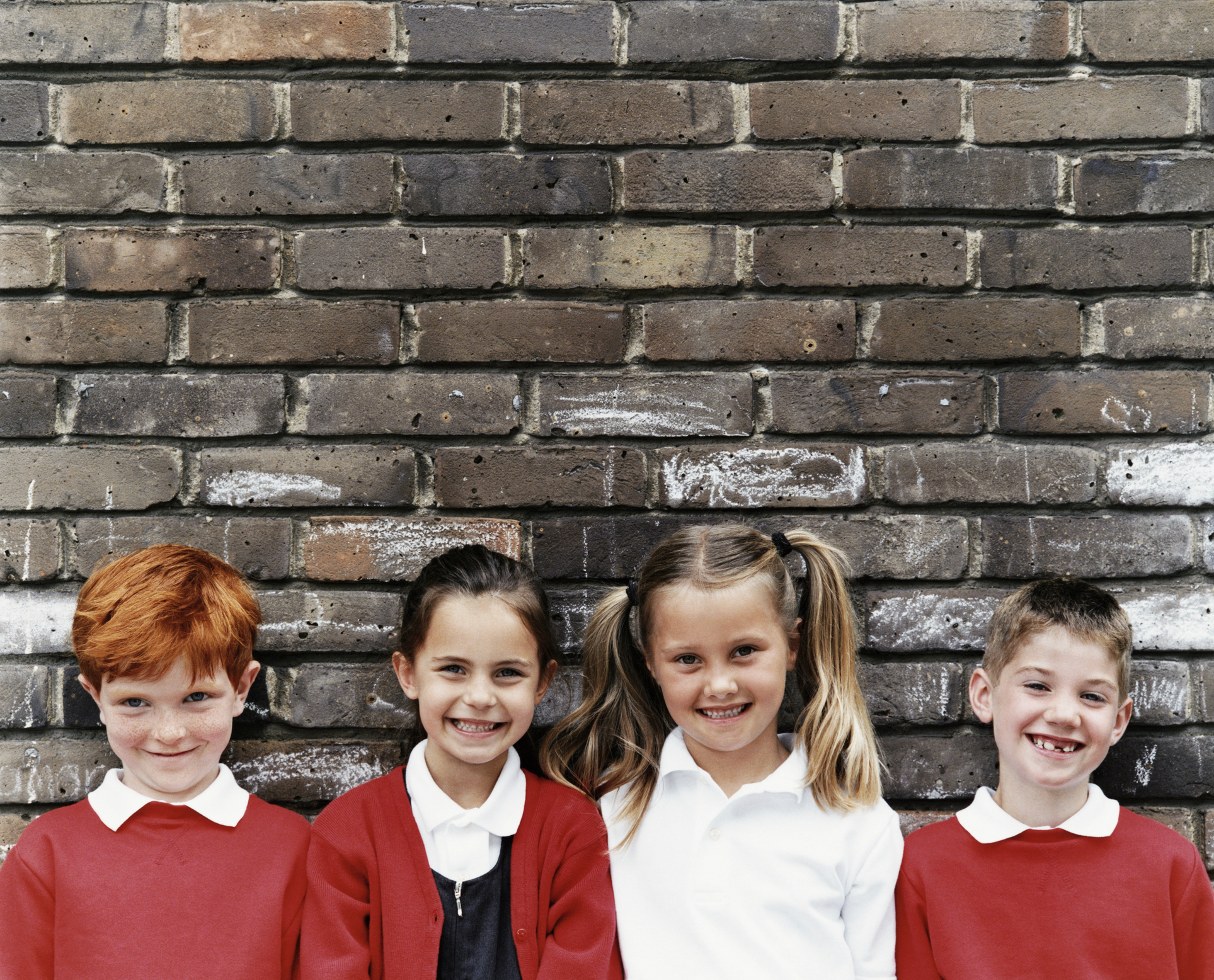 Four primary school children standing with their backs against a wall (Thinkstock/PA)