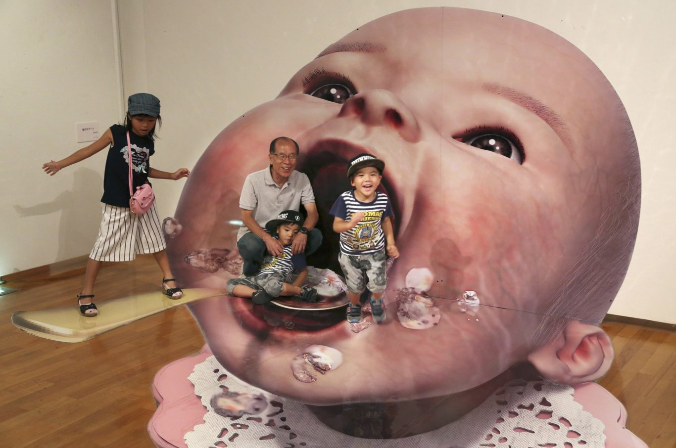 Visitors pose for a photo with a 3D image at a 3D trick art exhibition by Japanese artist Masashi Hattori in Kawasaki (Koji Sasahara/AP/PA)