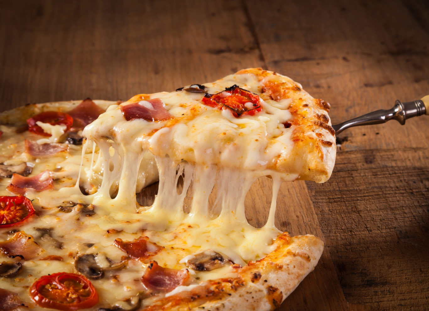 A slice of pizza is pulled from the whole