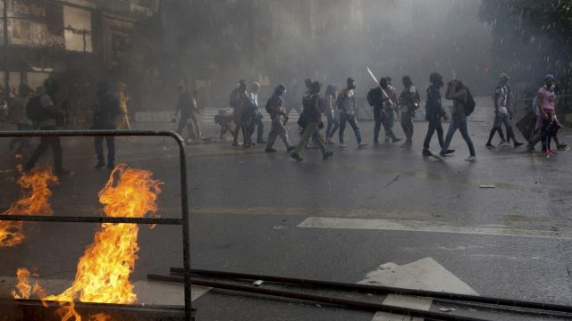 Masked anti-government demonstrators walk next to burning barricade during a protest against the installation of a constitutional assembly in Caracas