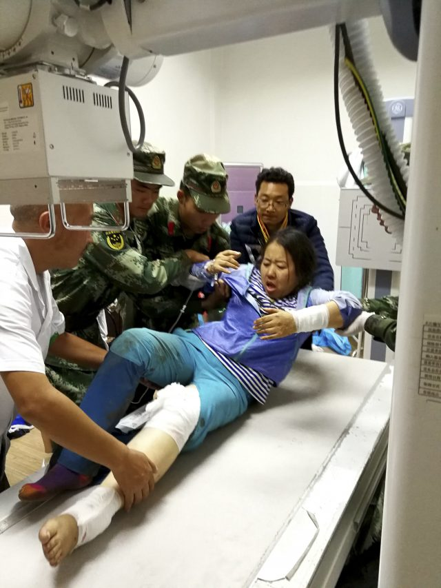 Rescue workers assist an injured woman onto a hospital bed (Chinatopix Via AP)