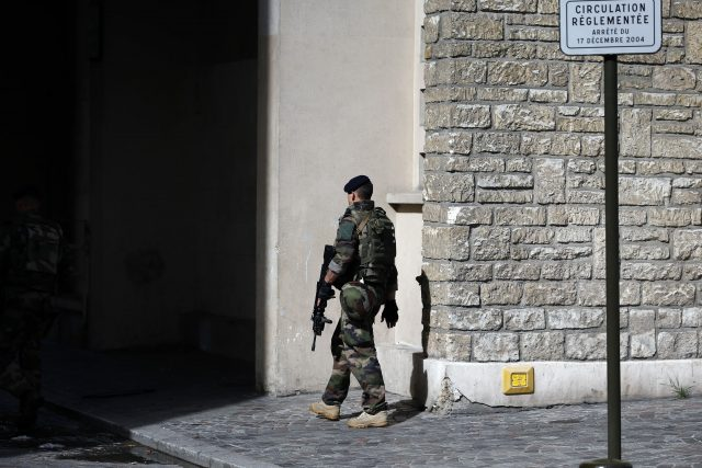 A French soldier patrols near the scene