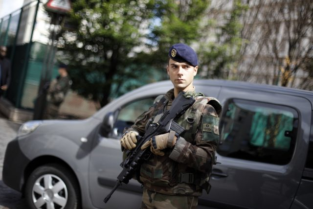 A French soldier stands near the scene where French soldiers were hit and injured by a vehicle in the western Paris suburb of Levallois-Perret (Kamil Zihnioglu/AP)