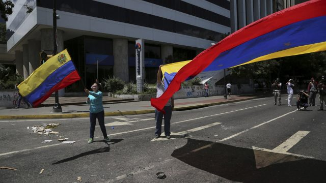 Anti-government demonstrators wave Venezuelan national flags during a protest against Venezuela's President Nicolas Maduro in Caracas