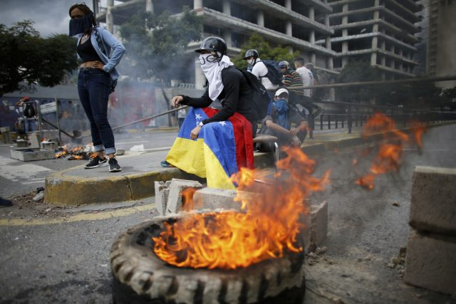 Masked anti-government demonstrators stand next to a burning tyre in Caracas (Ariana Cubillos/AP)