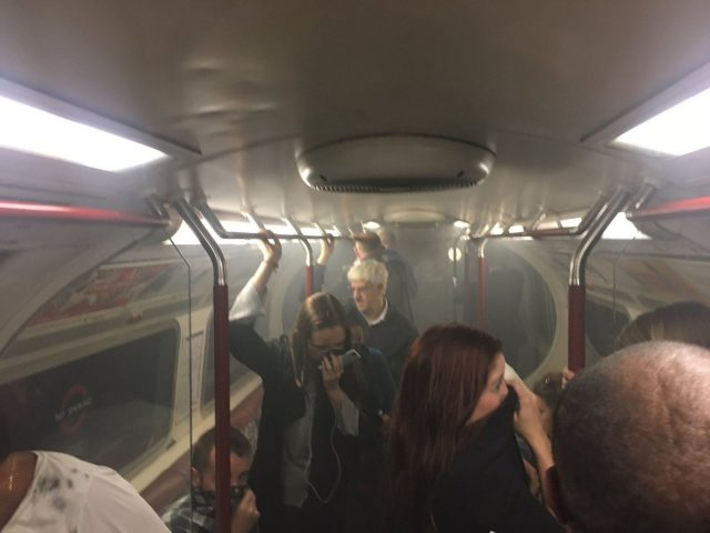 Commuters cover their mouths as smoke fills the carriage (Joe Bunting)
