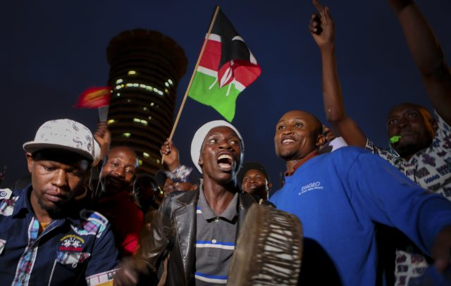 Supporters of Kenya's President Uhuru Kenyatta hold a Kenyan flag