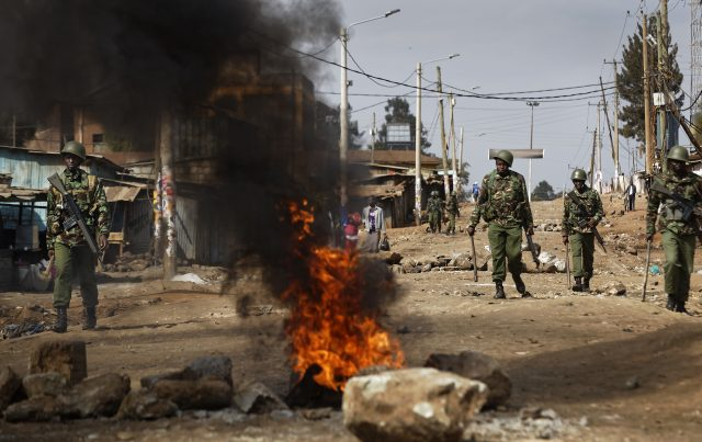 Riot police walk past burning barricades erected during clashes in the Kawangware slum of Nairobi