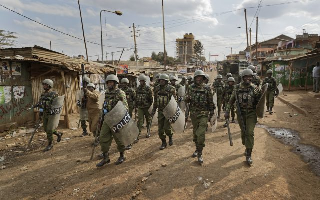 Riot police advance towards protesters throwing rocks and erecting burning barricades during clashes in the Kawangware area of Nairobi