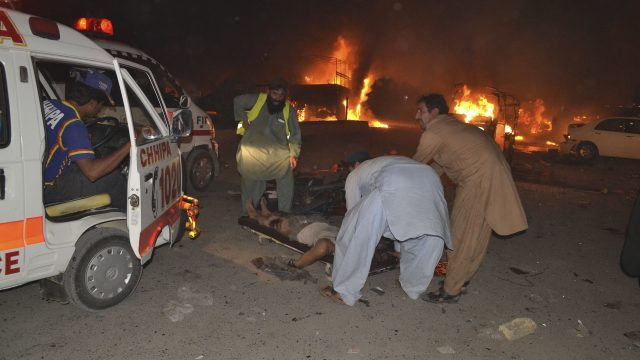 Volunteers help an injured person awaiting an ambulance to take them to a hospital in Quetta
